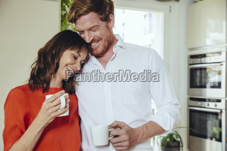 happy couple in kitchen holding coffee