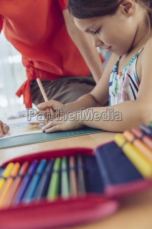 mother helping girl doing her schoolwork