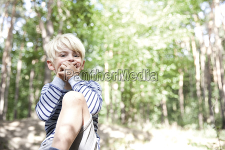 boy in forest covering his mouth
