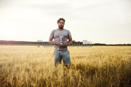 man standing in grain field holding