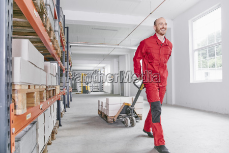 smiling man in warehouse pulling pallet
