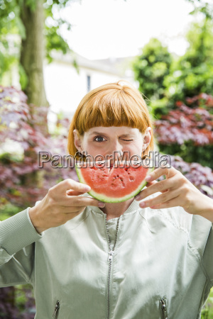 portrait of winking woman holding slice