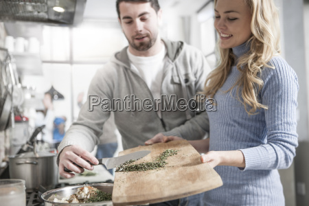 couple helping one another moving spices