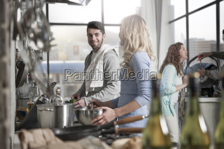 couple preparing food in kitchen with