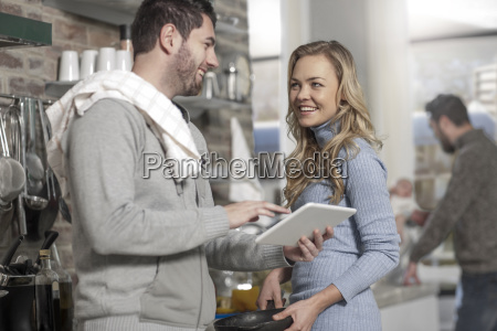 couple discussing with digital tablet recipe