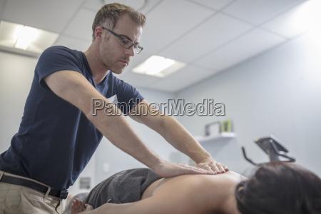 physio massaging womans back