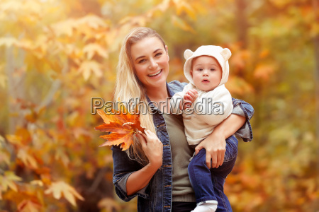 happy mother with baby in autumn