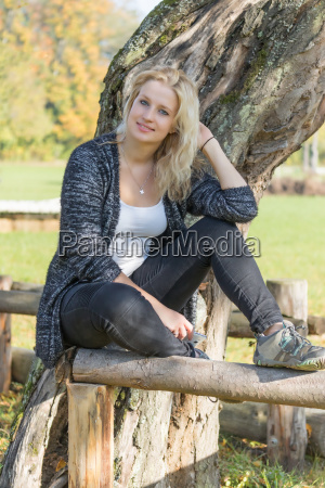 young woman sitting on the wooden