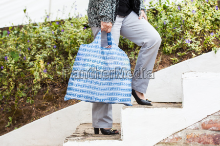woman carrying groceries in a reusable