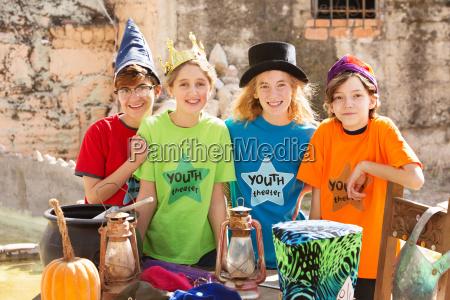 four friends pose by pumpkin
