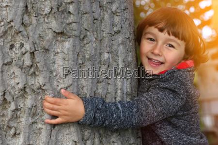 child hugs tree environmental protection love