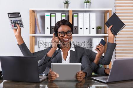 tired woman doing multitasking work on