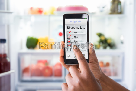 human hand marking shopping list on