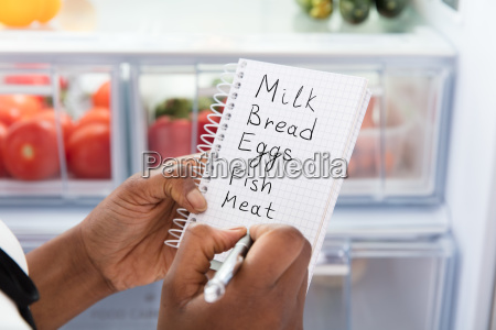 woman writing on shopping list near