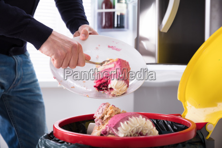 person throwing cake in trash bin