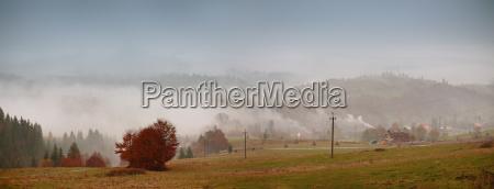 autumn fog in mountain village cloudy