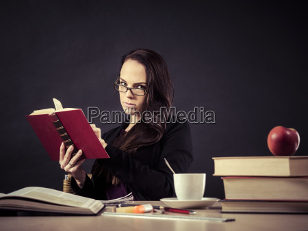 teacher, sitting, at, her, desk, reading - 23452455
