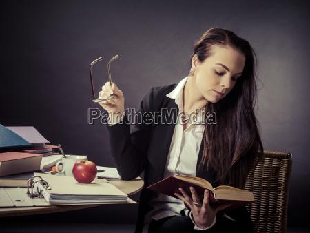 teacher, sitting, at, her, messy, desk - 23452457