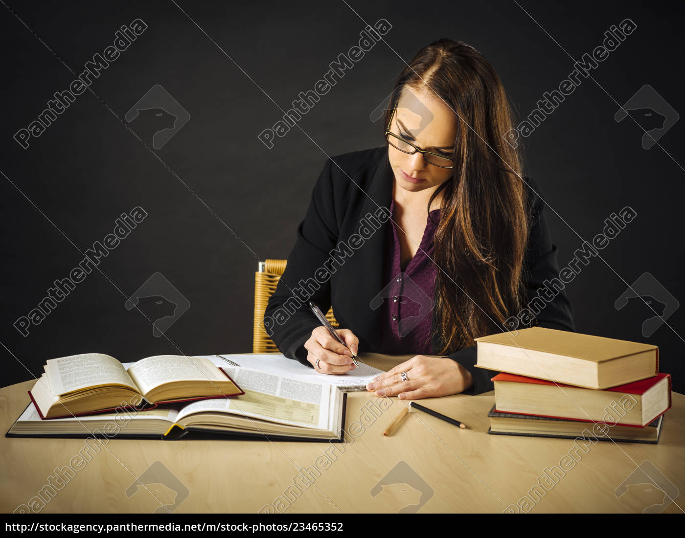 attractive, teacher, sitting, at, her, desk - 23465352