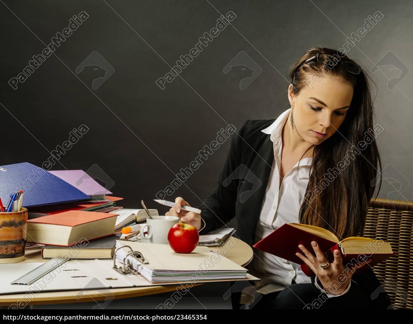 beautiful, teacher, sitting, at, her, desk - 23465354