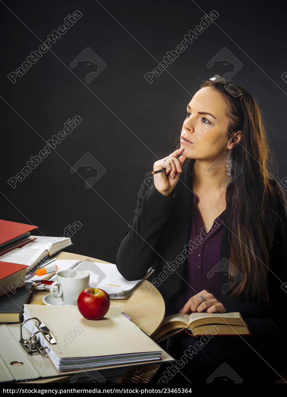 teacher, sitting, at, her, desk, thinking - 23465364