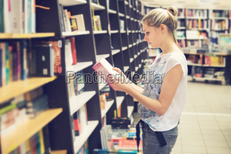 young, woman, choosing, a, book, to - 23474423