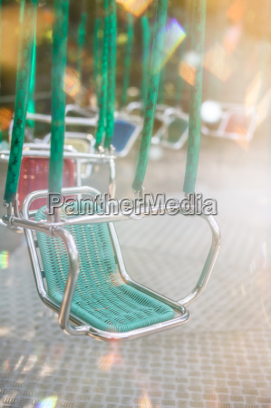 green empty carousel seat at summer