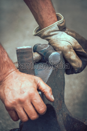a blacksmith resting his hands on