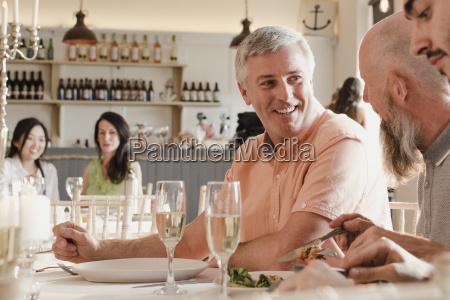 senior men socialising at a dinner