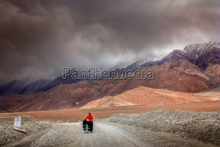 cyclist among stunning tibetan landscape