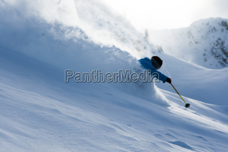 young man skiing through deep snow