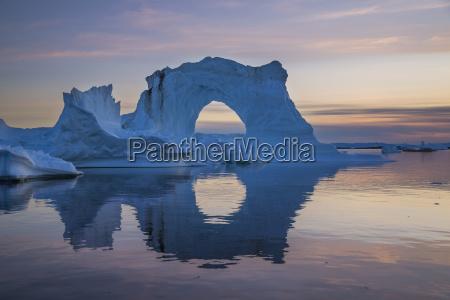natural arch of towering iceberg reflecting