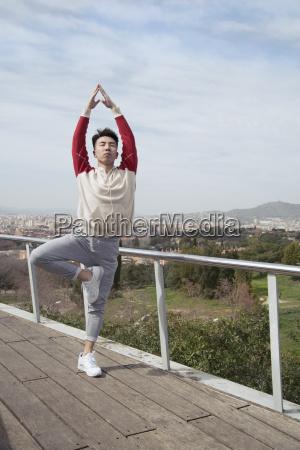 chinese man doing yoga in vrksasana