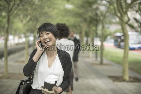 young asian woman carrying takeaway coffee
