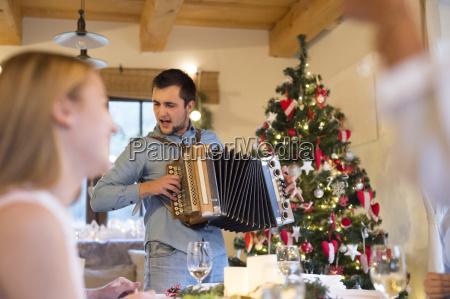 young man playing accordion at christmas
