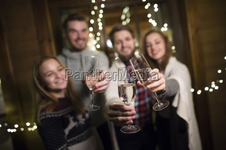 happy friends holding champagne glasses outdoors