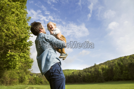 father holding happy baby in the
