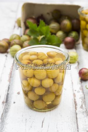 jar of preserved gooseberries and gooseberries