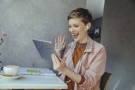 woman with tablet waving to somebody