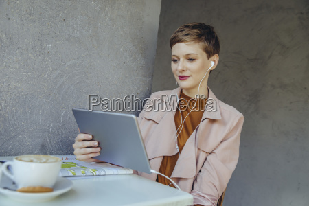 woman with tablet and earbuds in