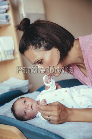 mother kissing her newborn baby girls