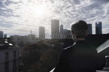 grey haired businessman on balcony looking