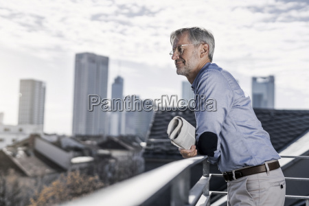 grey haired man standing on balcony