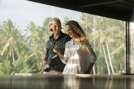 smiling couple with smartphone in design