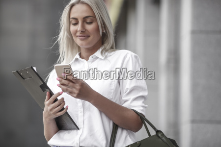 smiling businesswoman with clipboard and cell