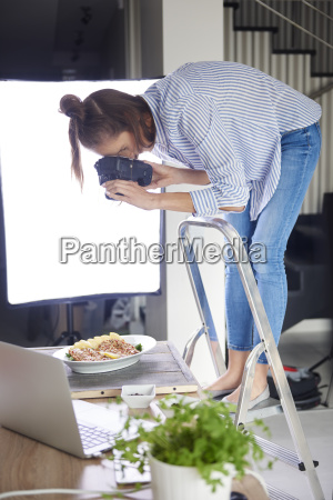 woman standing on step ladder and