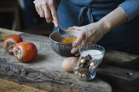 woman mashing persimmonfor preparing dessert