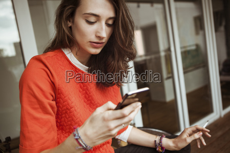 young woman checking smartphone on balcony