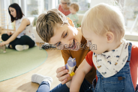 pre school teacher playing with toddler