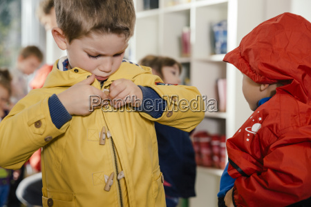 boy putting on his raincoat in